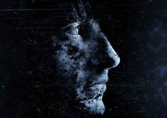 Man's face against black background.