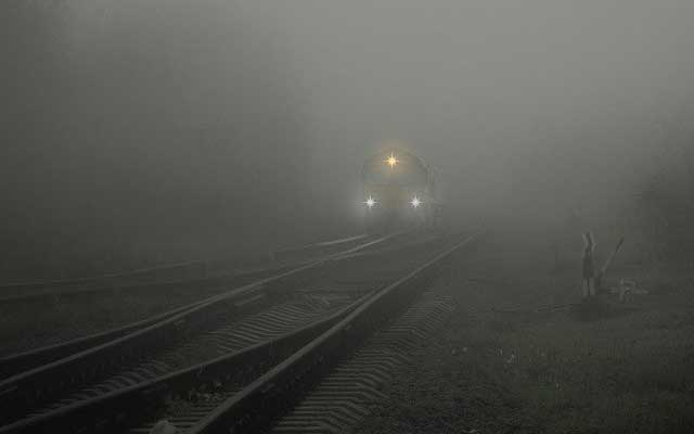 Train approaching in the fog